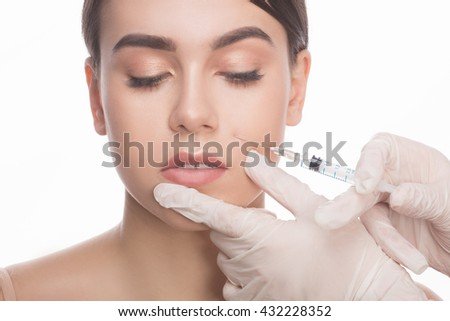 Doing botox injection. Beautiful young shirtless woman keeping eyes closed while doctors hand making injection in face.