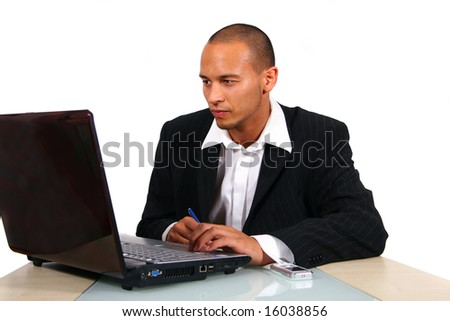 Doing Business A young businessman sitting by desk at office working on the laptop with cellphone on the table. - stock photo