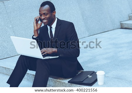 Doing business everywhere. Cheerful young African man in formalwear talking on the mobile phone and working on laptop while sitting on outdoors staircase - stock photo