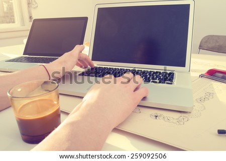 Doing some laptop work in office. - stock photo