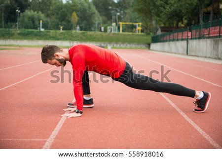 Doing some light stretching on a track. Athlete preparing for a run.