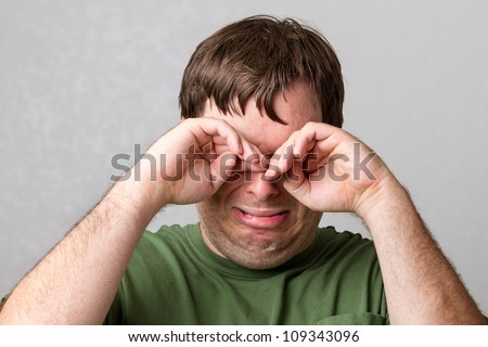 Doing the double fisted balling motion this guy is just crying his eyes out. - stock photo
