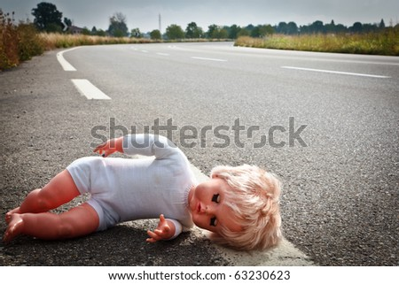doll leave on highway lane - stock photo