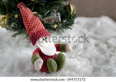 doll of santa claus with christmas tree in snow,cute stuffed toy Santa claus giving a christmas present - stock photo