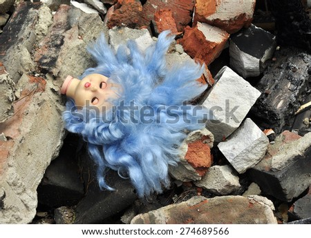 doll's head amid the debris of destroyed houses - stock photo