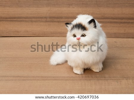 doll white cat on wooden background - stock photo