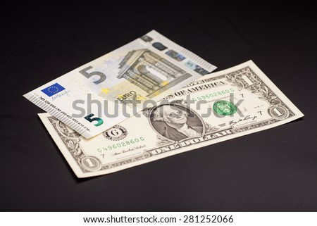 dollar and euro money isolated on black - stock photo