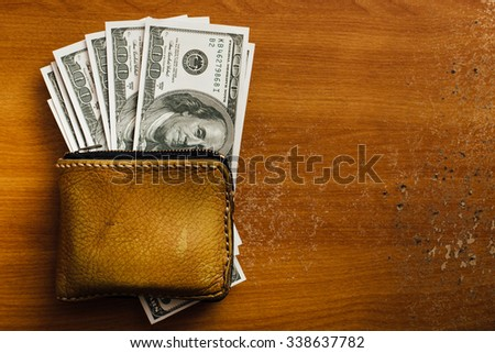 dollar and wallet on wooden table - stock photo