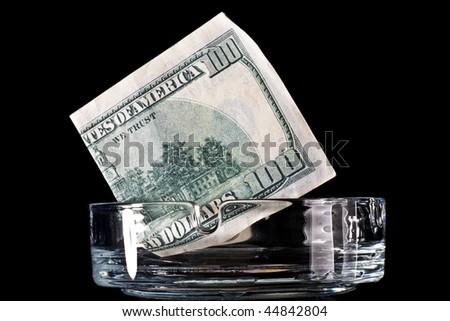Dollar banknote in ashtray ready to burning - stock photo