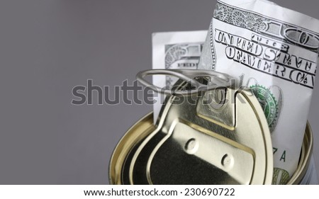 Dollar banknote in opened metal jar against gray background 100 bank note in moneybox Empty copy space for inscription Idea of saving from inflation