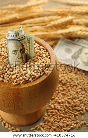 Dollar banknotes and wheat grains in bowl on wooden background. Agricultural income concept - stock photo
