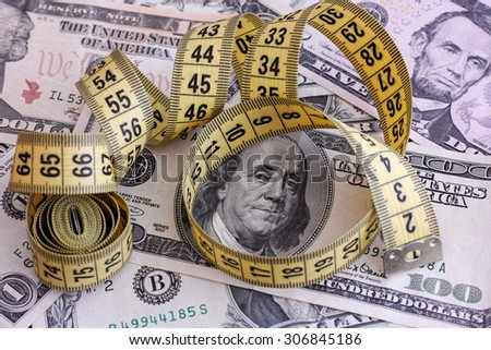 Dollar banknotes and yellow tape measure. Close up. - stock photo