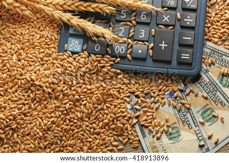 Dollar banknotes, calculator and wheat grains on wooden background. Agricultural income concept - stock photo