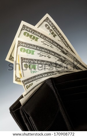 Dollar banknotes in leather wallet on dark background - stock photo