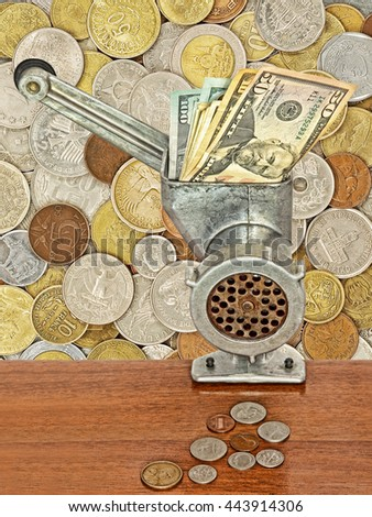 Dollar banknotes in meat grinder and coins on table on lot of different coins background.Money and business concept. - stock photo