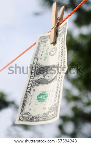 Dollar bill hanging from a cloth line depicting money laundry - stock photo