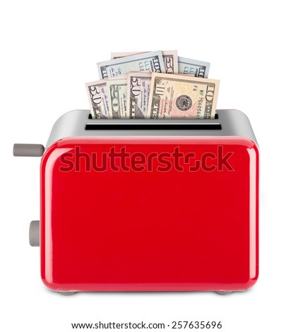 Dollar bills in a toaster. Isolated on white background. - stock photo
