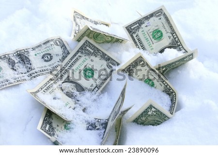 Dollar bills on the snow concept for frozen accounts - stock photo