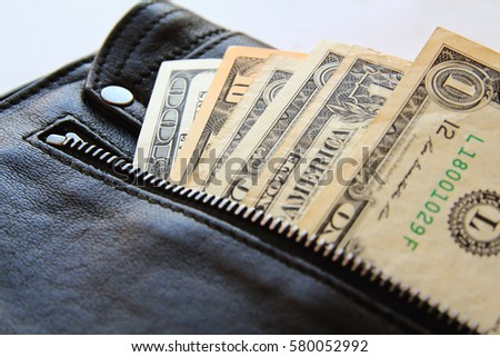 dollar bills peeking out of the black leather bag, close-up