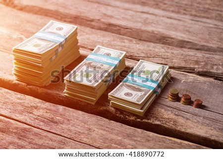Dollar bundles near coins. Small coins and cash. Money on old wooden shelf. From rags to riches. - stock photo