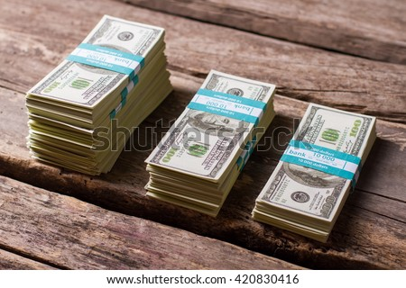 Dollar bundles on wooden background. Cash stacks of different size. Earned with hard labor. Money savings on old table. - stock photo