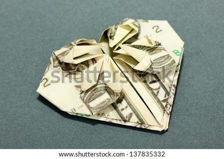 Dollar folded into shirt on blue background - stock photo