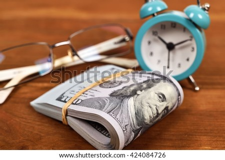 dollar, glasses  and alarm clock on wooden table - stock photo