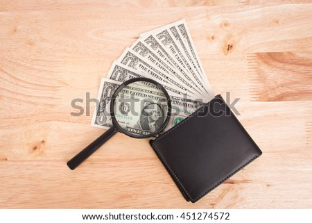 Dollar money in wallet and magnifier on wooden background - stock photo