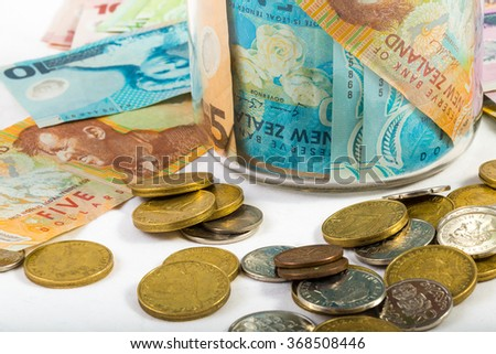 Dollar notes and coins in New Zealand currency in glass jar isolated on white - stock photo