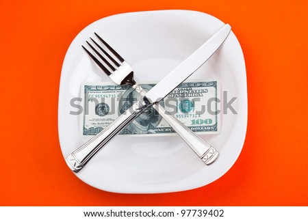 dollar on plate with fork and knife