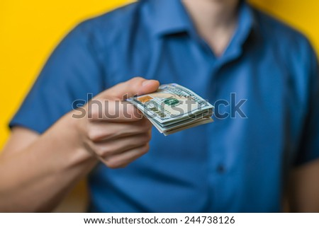 Dollars. A young man close-up in a blue shirt on a yellow background, gives or takes money. Holds money in hands. . Photos - stock photo