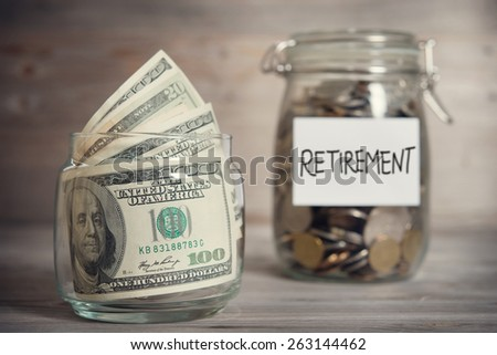 Dollars and coins in glass jar with retirement label, financial concept. Vintage tone wooden background with dramatic light. - stock photo