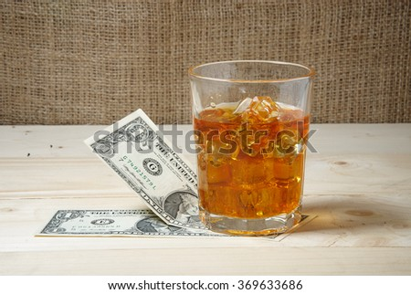 Dollars and glass of whiskey with ice on wooden table. Place for text