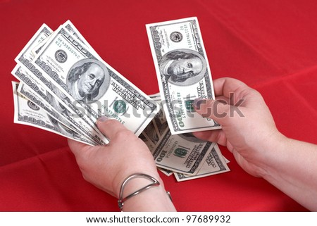 Dollars and hands on a red background