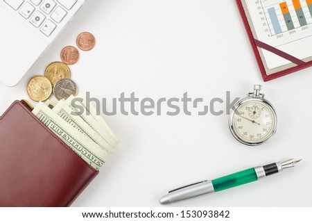 Dollars, computer, pen, timer and graphs for finance concept