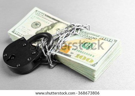 Dollars currency with lock and chain on grey background