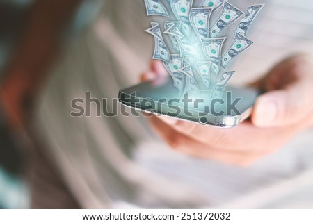 Dollars flying out of the smart phone.business concept - stock photo