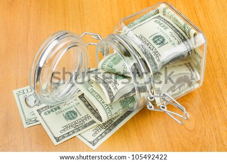 dollars in glass jar on table