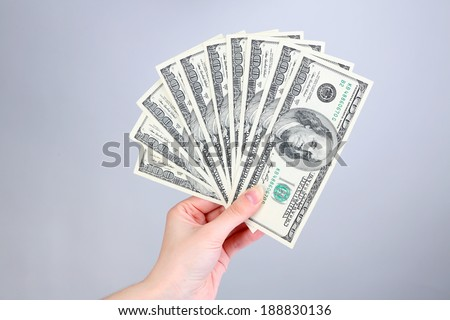Dollars in hand on grey background