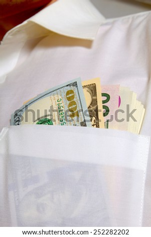 Dollars in the pocket of his white shirt. - stock photo