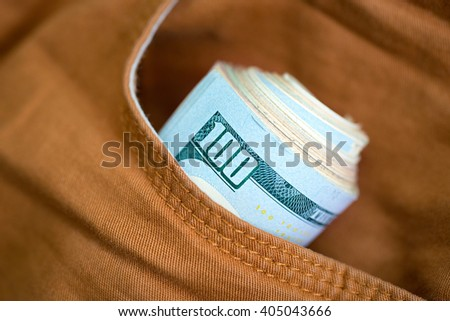 Dollars in the pocket of jeans. Bundle of dollars. Money in the pocket of trousers. Business casual.  - stock photo