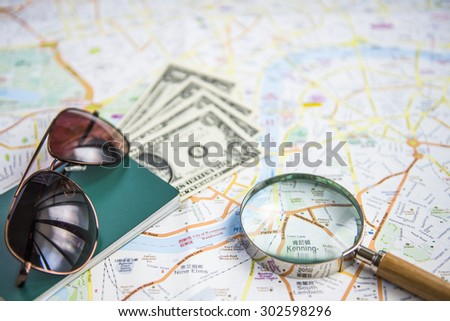 Dollars, magnifying glass, passport, sunglasses and a world map - stock photo