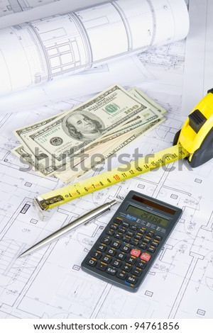 Dollars, measurement tape and calculator on architectural drawing blueprint