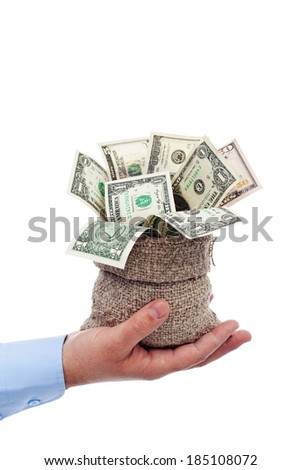 Dollars overflowing from a bag held in businessman hand