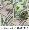 dollars rolled up with rubberband isolated on money background  - stock photo
