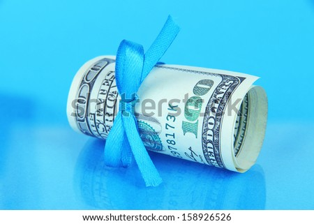 Dollars with gift bow on blue background - stock photo