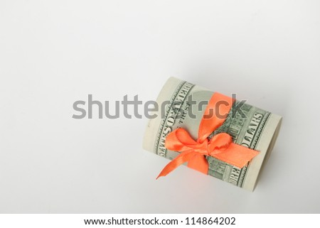 Dollars with orange ribbon over light gray background - stock photo