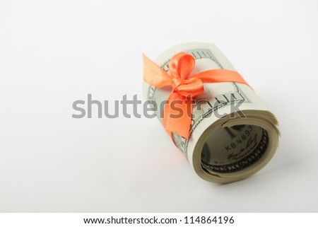 Dollars with orange ribbon over light gray background as a present concept - stock photo