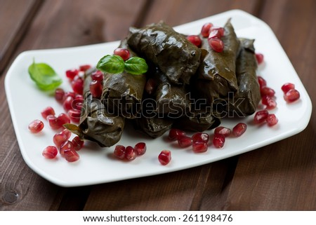 Dolmades with pomegranate on a glass plate, studio shot - stock photo
