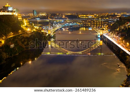 Dom Luis bridge reflected in Duoro river at night. Porto, Portugal - stock photo